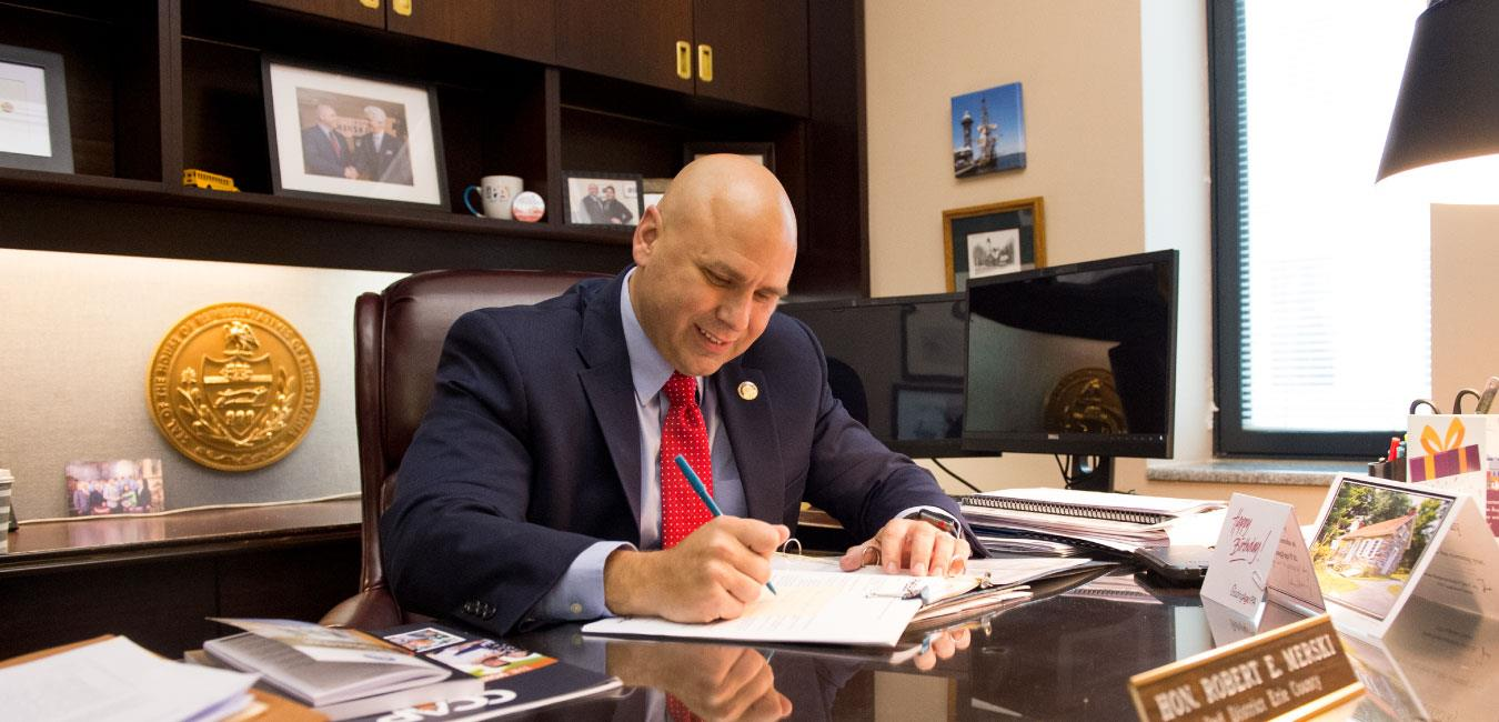 Representative Merski writing on paper at desk in his office